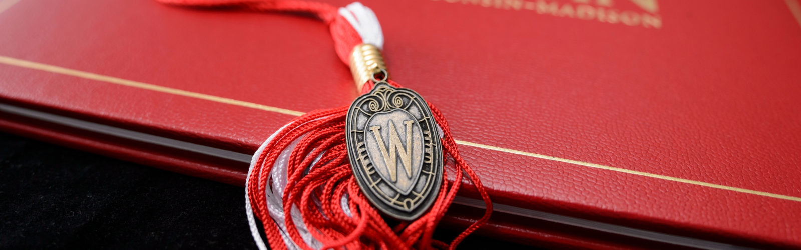 A graduation tassel with a UW Madison diploma.